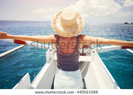 Young woman with hat traveling on the boat in ocean