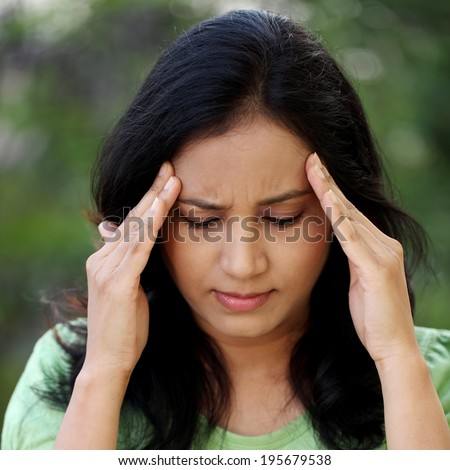 Young woman with headache holding her hand to the head