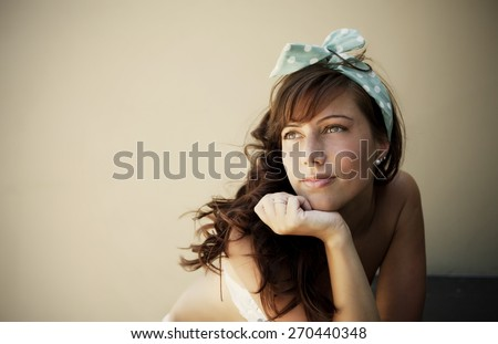 Young woman with headband relaxing outdoors - stock photo