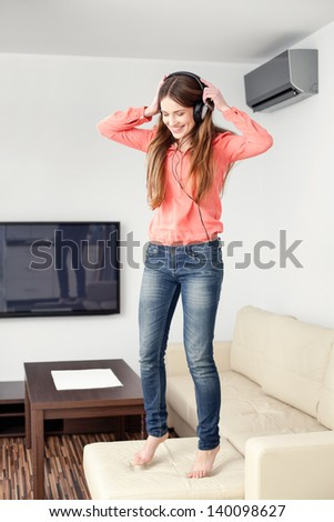 Young woman with headphones jumping on couch in living room. She is listening to music
