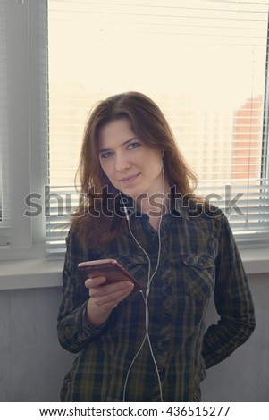 young woman with headphones listening to music. the white balance is incorrect.