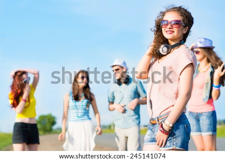 young woman with headphones on a background of blue sky and funny friends - stock photo