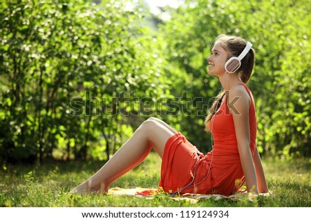 Young woman with headphones on green grass in the park