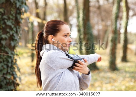 Young woman with headphones preparing for a jogging in autumn park, she is stretching her arm.