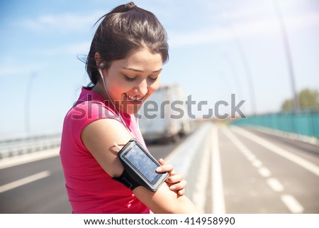 Young woman with headphones preparing for a jogging, she is looking at mobile phone.