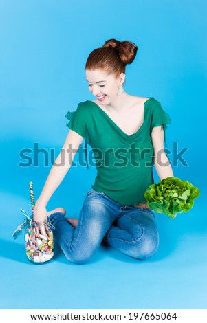 Young woman with healthy and unhealthy food like salad and candy in studio - stock photo