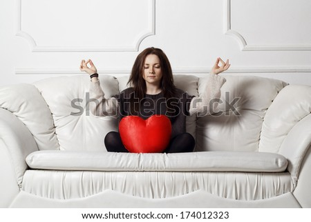Young woman with heart doing meditation