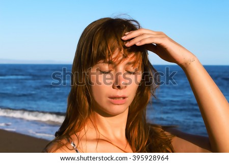 Young woman with heatstroke, sunstroke on a beach, healthy lifestyle on vacation, medicine on vacation, dangerous sun, beach life, girl under sun, red hair girl on beach by blue sea, holiday health - stock photo