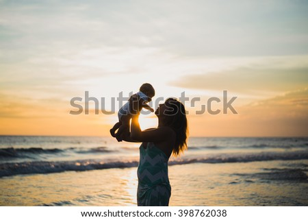 young woman with her baby on the beach during sunset . Mother with her baby on the beach watching the sunset. - stock photo