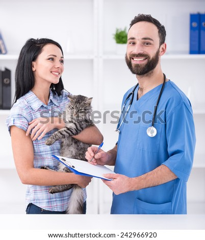 Young woman with her cat on a visit to the vet. - stock photo