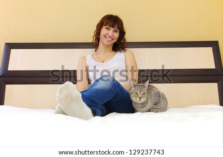 young woman with her cat on the bed at home