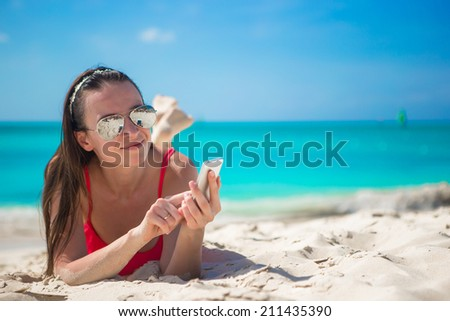 Young woman with her cell phone on exotic beach - stock photo