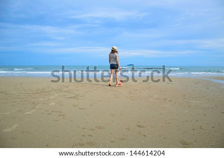 Young woman with her cute jack russel puppy on the beach, Thailand