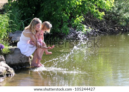 young woman with her daughter splashes water at the lake