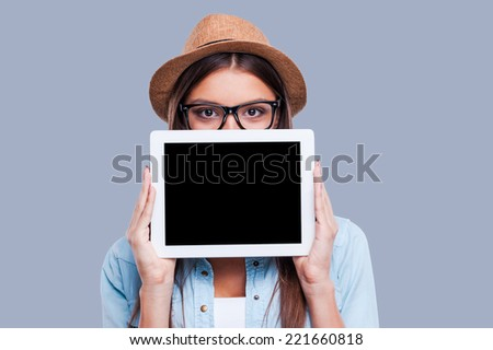 Young woman with her digital tablet. Young women holding her digital tablet in front of her face while standing against grey background - stock photo