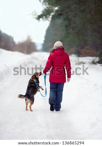 Young woman with her dog walking on the snowy road