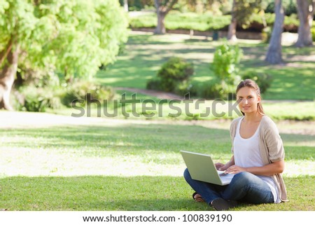 Young woman with her laptop sitting in the park