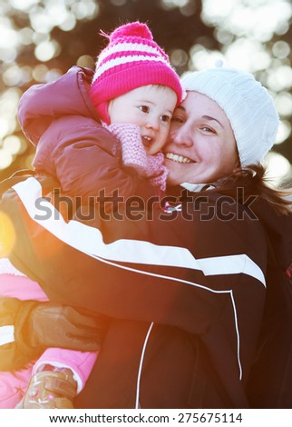 Young woman with her lovely child outdoor in winter - stock photo