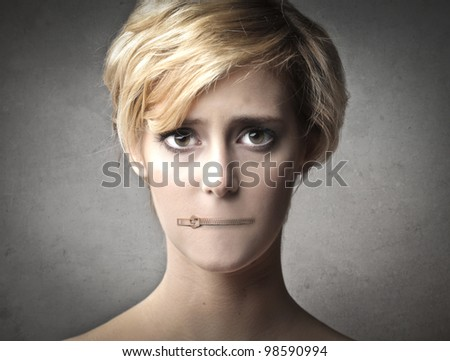 Young woman with her mouth closed by a zipper - stock photo