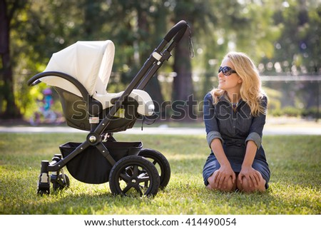 Young woman with her newborn baby enjoying sunny summer day in the park. Mother with child in the stroller outdoors. Motherhood.  Mum with baby walking in the city. - stock photo