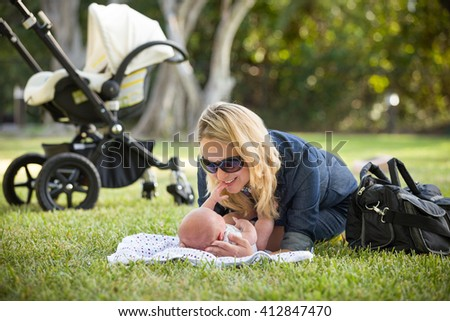 Young woman with her newborn baby lying on the grass in the park and enjoying sunny summer day. Mother with child outdoors. Motherhood. - stock photo