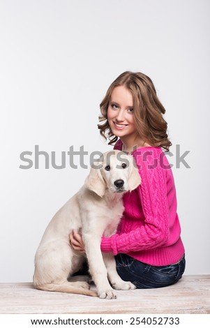 Young woman with her pet, golden retriever in studio