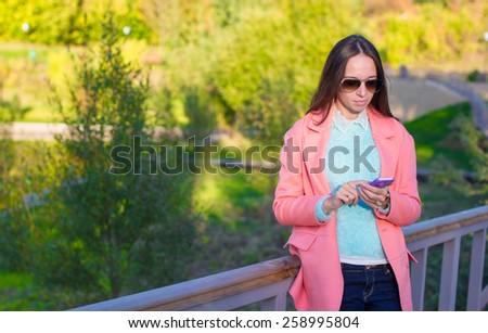 Young woman with her phone at autumn day - stock photo