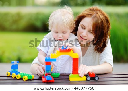 Young woman with his toddler son playing with colorful plastic blocks  - stock photo