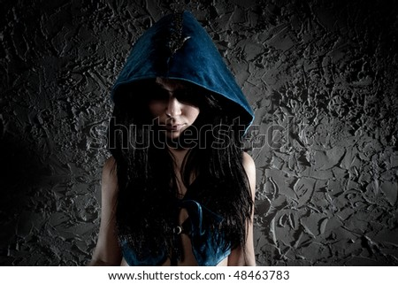 Young woman with hood on head. Dark contrast colors. - stock photo