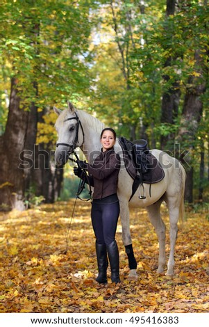 Young woman with horse in autumn woods
