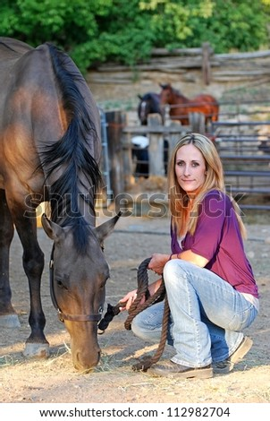 Young woman with horse in corral area with other horses in the background. - stock photo