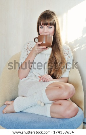 young woman with hot drink at home