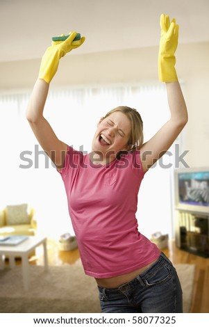 Young woman with housecleaning gear dances in the living room.  Vertical shot.