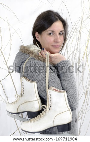 young woman with ice skates , outdoors in the snow - stock photo