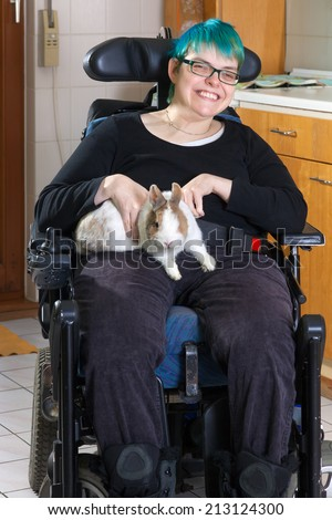 Young woman with infantile cerebral palsy due to birth complications confined to a multifunctional wheelchair caressing a pygmy rabbit as part of her therapy giving the camera a charming smile - stock photo
