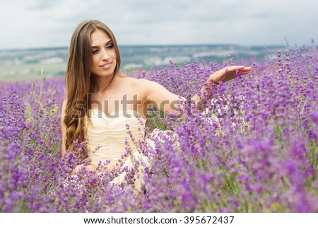 Young woman with is wearing nice white dress at field of purple lavender flowers