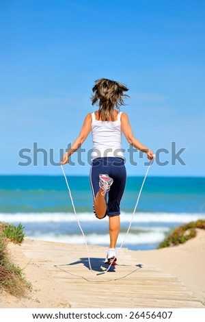 young woman with jumping rope on the beach - stock photo