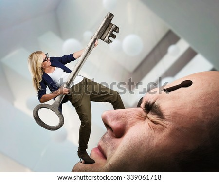 Young woman with key on the man's face with keyhole - stock photo