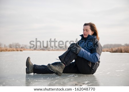 Young woman with knee injury on frozen icy lake - stock photo