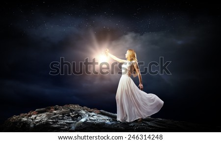 Young woman with lantern walking in dark forest - stock photo