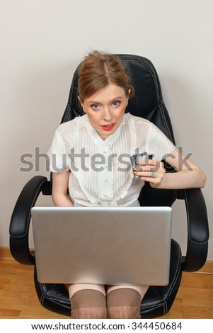 Young woman with laptop and credit cards in her hand shopping on the internet