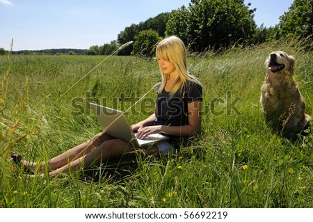 young woman with laptop and dog on a meadow - stock photo