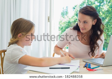Young woman with laptop assisting daughter in homework at table