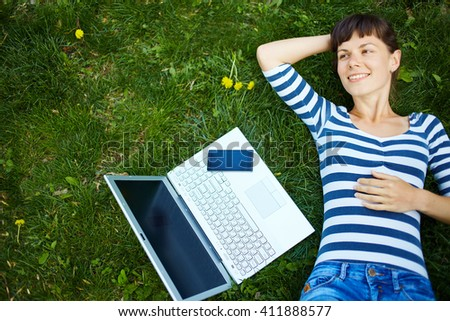 young woman with laptop computer and phone on the grass in park. remote work or freelance concept