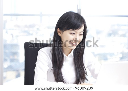 Young woman with laptop computer in her office - stock photo