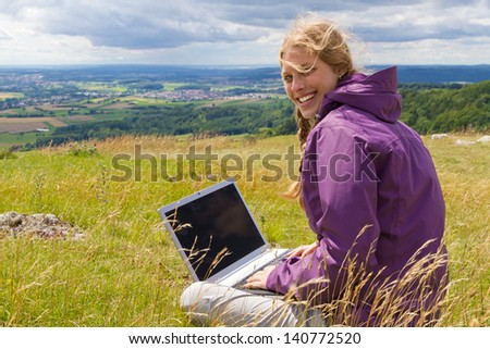 Young woman with laptop in nature  - stock photo