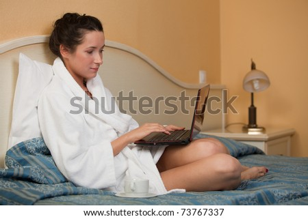 Young woman with laptop lies on the bed at home. - stock photo