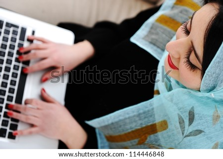 Young woman with laptop on couch - stock photo
