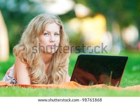 Young woman with laptop on green grass at park