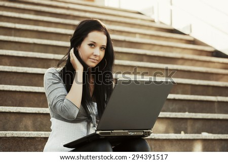 Young woman with laptop on the steps